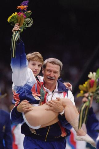 Coach Bela Karolyi carries an injured yet triumphant Kerri Strug of the United States