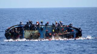 People try to jump in the water right before their boat capsizes off the Libyan coast,