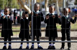 Children wearing school uniforms watch the laying of wreaths, at the Hector Pieterson Memorial in Soweto, South Africa,
