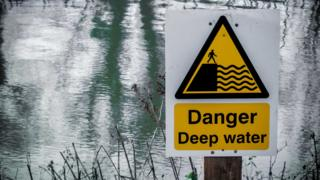 "Sign reading ""Danger Deep Water"" by a lake"