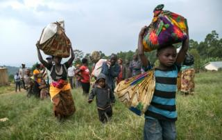 Congolese people carry their belongings after they crossed the border from the Democratic Republic of Congo to be refugees at Nteko village in western Uganda on January 24, 2018.