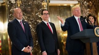 Cohn standing beside Trump