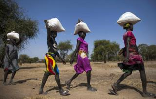 "Women carry food in gunny bags after visiting an aid distribution centre in Ngop in South Sudan""s Unity State on March 10, 2017. The Norwegian Refugee Council (NRC) distributed food (maize, lentils, oil and corn soya blend) for more than 7,100 people in Ngop. South Sudan,"