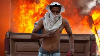 A person runs during clashes between opponents of Venezuelan President Nicolas Maduro and members of the Bolivarian National Guard of Venezuela