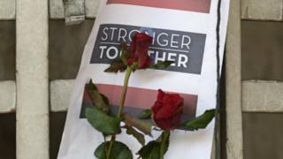 """A sign left outside the Erawan shrine in Bangkok. After a speech by the country's prime minister, the slogan """"Stronger Together"""" started picking up in popularity online."""