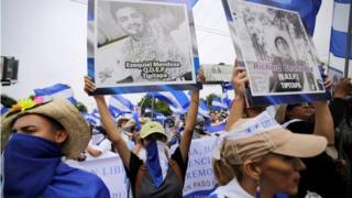 Demonstrators hold up pictures of students killed during the anti-government protests, while taking part in a march to demand the ouster of Nicaragua's President Daniel Ortega in Managua, Nicaragua, July 23, 2018.