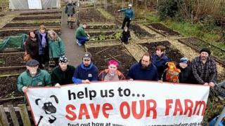 Campaigners to keep the farm open holding a banner