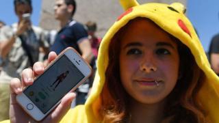 Una joven con un traje de Pikachu y su teléfono, en el que juega Pokémon Go