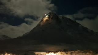 Helicopter lights up Buachaille Etive Mor