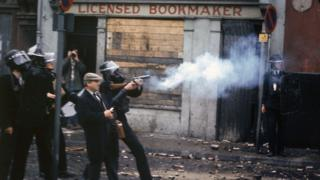 Police officers wearing gas masks fire cartridges of tear gas in front of a bookmakers in Derry