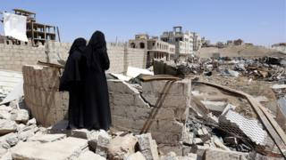 Two Yemeni women inspect the site of an alleged Saudi-led airstrike hit a neighbourhood two days earlier, damaging nearby schools, in Sanaa