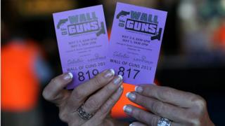 A woman tries to sell raffle tickets to win a gun from the 'Wall of Guns' during the 2013 NRA Annual Meeting and Exhibits at the George R. Brown Convention Centre on 4 May 2013 in Houston, Texas.