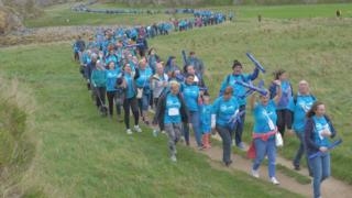 Thousands of walkers snake their way along the route
