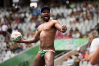 in_pictures A South African rugby supporter wearing flag-print swimming trunks throws the ball.