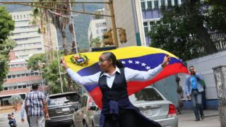 A woman holds a Venezuelan flag during a demonstration - 30 January 2019
