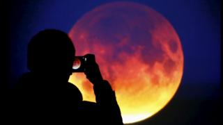 A man taking a picture of the lunar eclipse