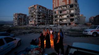 Residentes en Sarpol-e Zahab sentados en torno a una hoguera frente a edificios destruidos.