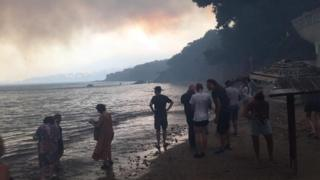 People on the coast in Greece to escape the fire