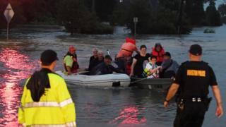 Спасатели на лодках перевозят постарадавших от наводнения в Хьюстоне