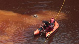 Forensic officers, rescuers and divers retrieve a suitcase, which police say contains a female body