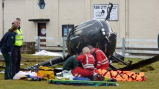 Man being treated beside damaged helicopter