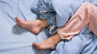 Pernas inquietas de pijamas sob um lençol