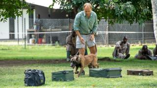 Will Powell holds a Malinois dog by a lead as it walks past luggage laid out on the grass during training in Arusha, Tanzania