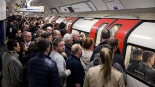A crowded tube platform as commuters wait to board