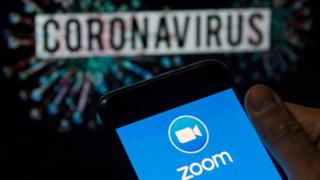 Zoom logo seen displayed on a smartphone with a computer model of the COVID-19 coronavirus on the background.