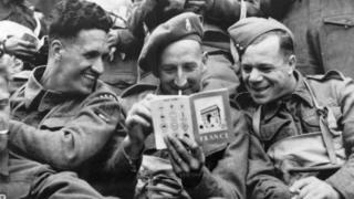 Британські солдати читають путівник Францією для туристів на борту десантного катера, що прямує до Нормандії, пролив Ла-Манш, 1944 рік