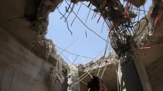 Man inspects building damaged in reported Saudi-led coalition air strike in Saada province, Yemen (10 September 2016)