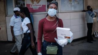 A woman sells surgical mask on the streets in Nairobi for 200 shillings each