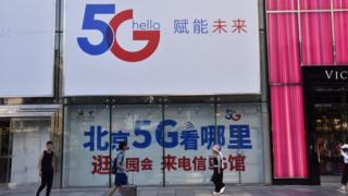People pass a China Telecom 5G ad on July 25, 2019 in Beijing, China