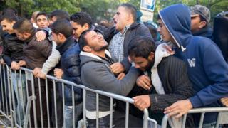 Migrants wait to be registered for accommodation in Berlin (29 Sept)