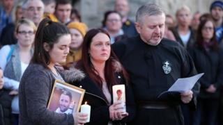 Fr Gary Donegan at a vigil for murdered man Michael McGibbon, with the victim's widow Joanne