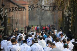 Young Israelis walk under the infamous German inscription that reads 'Work Makes Free' at the main gate of the Auschwitz I extermination camp in November 2014