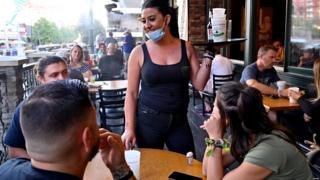 Waitress serves customers while masked