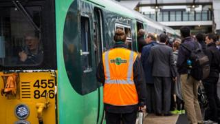 A Southern rail conductor waits as commuters board a train at East Croydon station