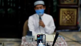 An imam in Indonesia broadcasts a recitation of the Koran