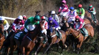 Horses and riders jump Canal Turn during the 2018 Grand National at Aintree Racecourse on April 14, 2018