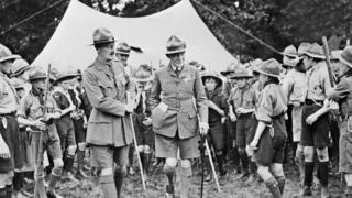 Baden-Powell (C-R) surrounded by the members of the Boy Scout movement