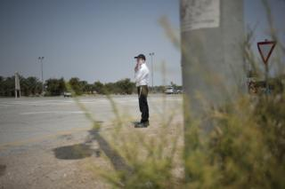 An Orthodox Jewish man looks out for arriving cars as he waits for the bus at the Nahshon bus junction in Nahson, Israel