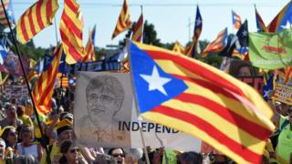 """People hold a portrait of ousted Catalan regional president Carles Puigdemont (C) while waving Catalan pro-independence """"Estelada"""" flags and banners during a demonstration at the European Parliament on July 2 , 2019"""