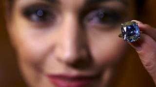 A model poses with the 12.03 carat cushion-shaped Blue Moon diamond (11 November 2015)