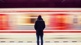 شاب ينظر إلى قطار يسير بسرعة كبيرة