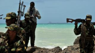 Armed militiamen and a pirate walk on a rocky outcrop on the coast in the central Somali