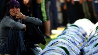 A Bosnian Muslim woman mourns by the caskets of 33 newly identified bodies of the 1995 Srebrenica massacre, on 11 July 2019