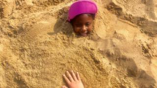 A girl smiles as she is partially buried on an excursion to a beach in Broadstairs, Kent