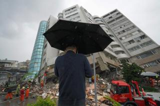 A man prays outside a building which tilted to one side after its foundation collapsed in Hualien