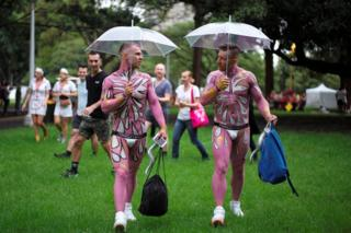 Two men in full pink bodypaint use umbrellas in the Sydney Gay and Lesbian Mardi Gras festival, arriving during early rain showers in Sydney, Australia March 4, 2017.